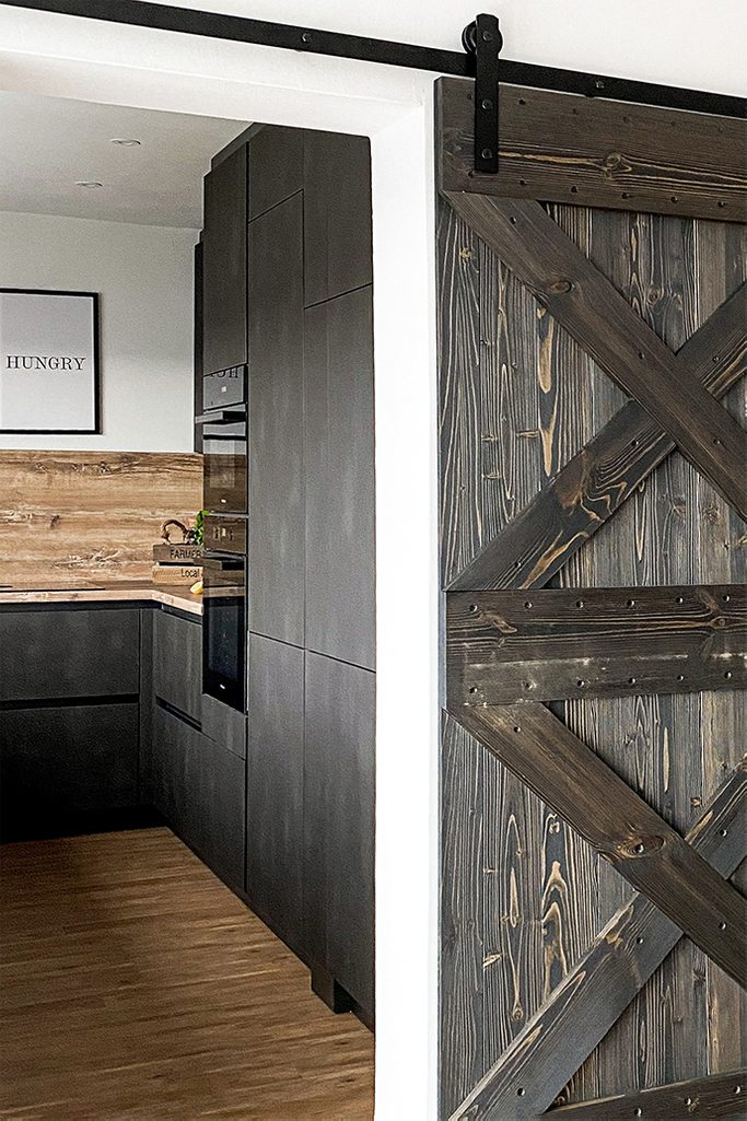 Wejście do kuchni z ciemną zabudową oddzielone drewnianymi drzwiami przesuwnymi w stylu rustykalnym