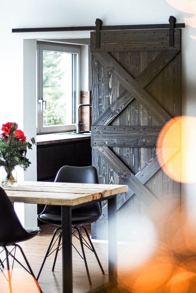 Drewniane drzwi przesuwne w ciemnym kolorze zamontowane w przejściu między jadalnią a kuchnią