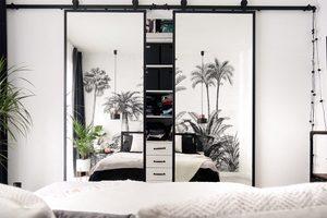 Podwójne drzwi przesuwne z lustrem prowadzące z sypialni do garderoby