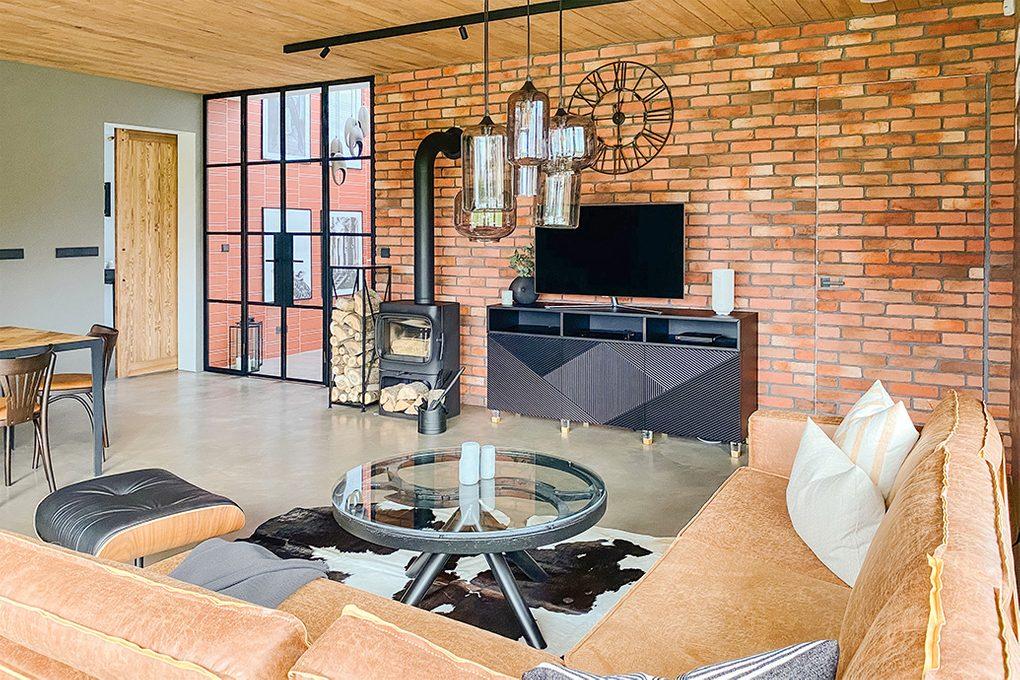 Loftowo-industrialny salon z czarnym kominkiem i cegłą na ścianie