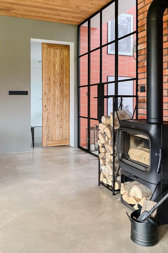 Czarny, metalowy kominek koza w salonie urządzonym w stylu industrialnym.