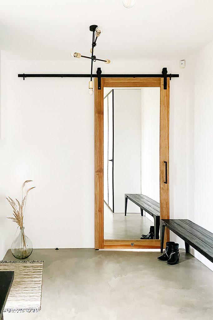 Duże lustro z drewnianą ramą w przedsionku z białymi ścianami i czarnymi elementami dekoracyjnymi