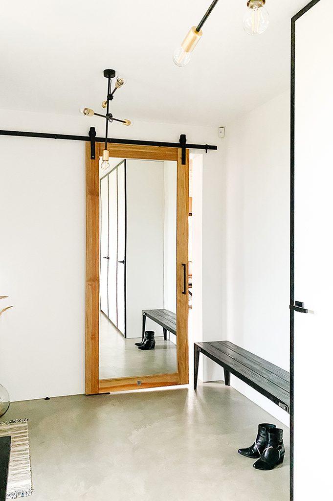 Przedsionek w stylu minimalistycznm z dużym lustrem przesuwnym i lampą industrialną