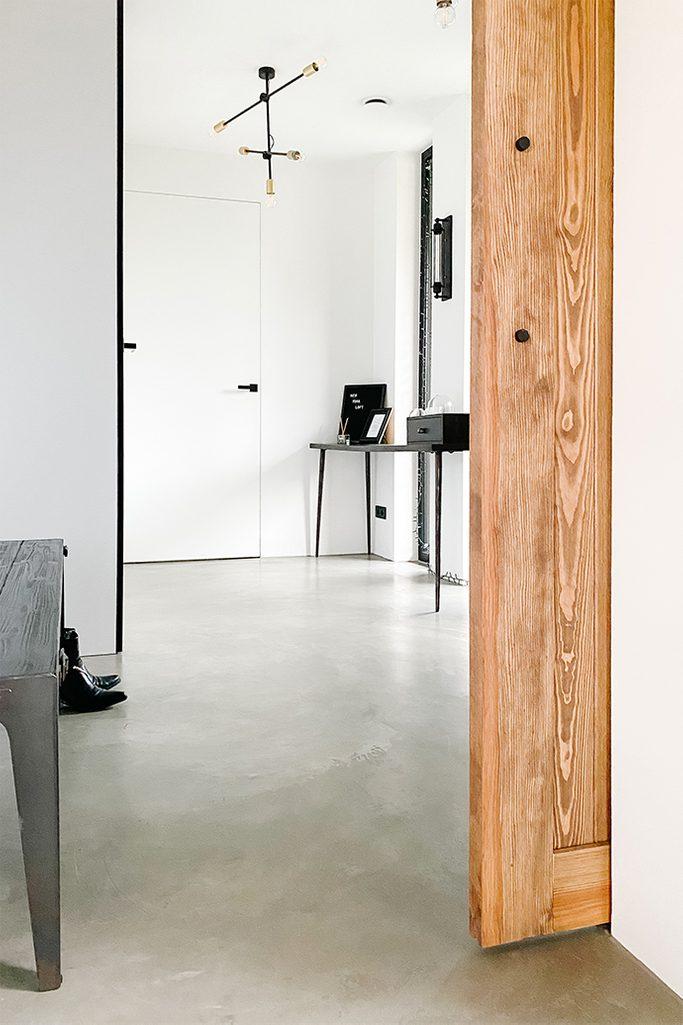 Uchylone drzwi do przedsionka urządzonego w bieli i czerni z cementową podgłogą