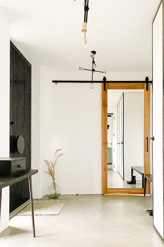 Industrialna lampa, czarny minimalistyczny stolik i drzwi przesuwne z lustrem w wiatrołapie