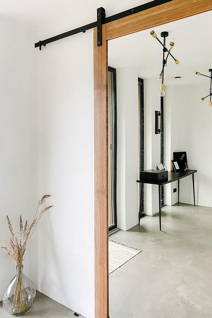 Industrialny żyrandol i czarny minimalistyczny stolik w odbiciu lustrzanym