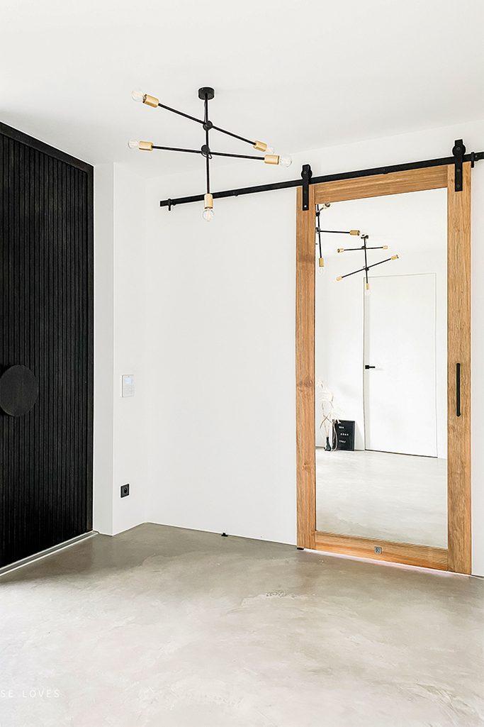 Białe pomieszczenie z mikrocementową podłogą oraz industrialnym żyrandolem