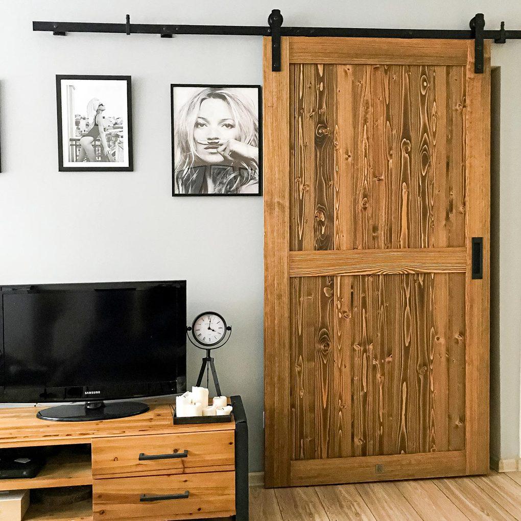 Drewniane drzwi na czarnym systemie przesuwnym zamontowane na ścianie udekorowanej czarno-białymi plakatami