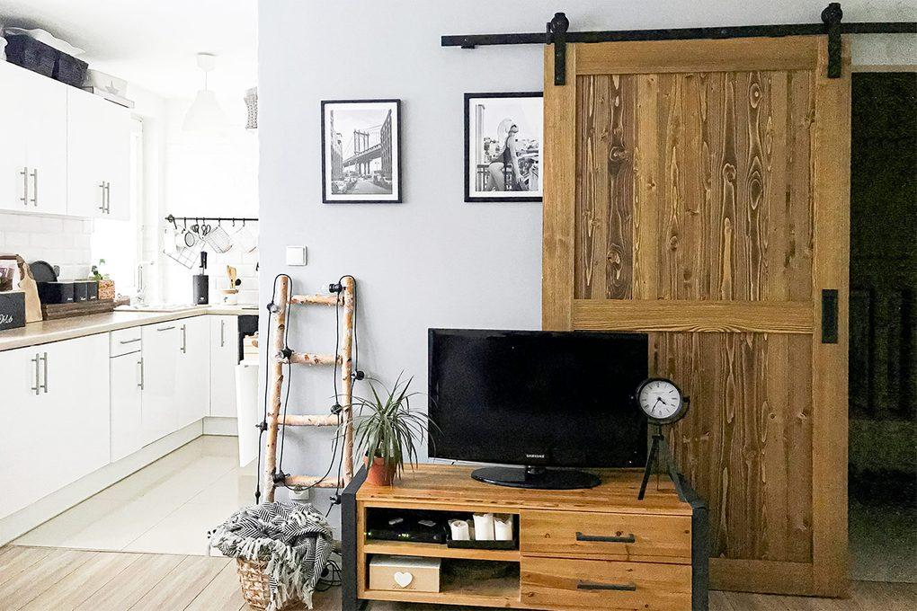 Drzwi przesuwne w małym mieszkaniu udekorowanym w bieli, drewnie i czarnych dodatkach