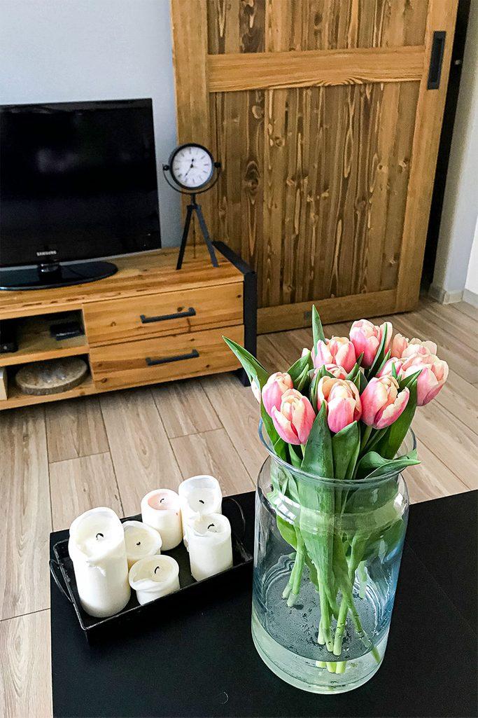 Bukiet tulipanów na tle drewnianych drzwi i drewnianej szafki z telewizorem