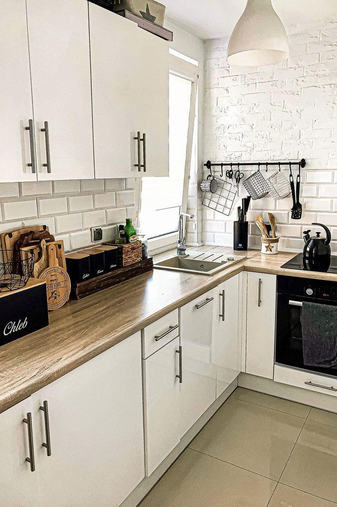Kuchnia z białymi szafkami z drewnianym blatem, białą ceglaną ścianą i czarnymi akcesoriami kuchennymi