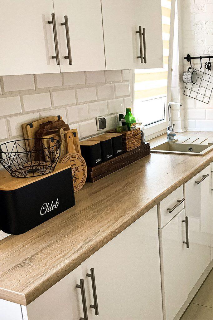 Białe szafki kuchenne z drewnianym blatem i czarnymi akcesoriami kuchennymi