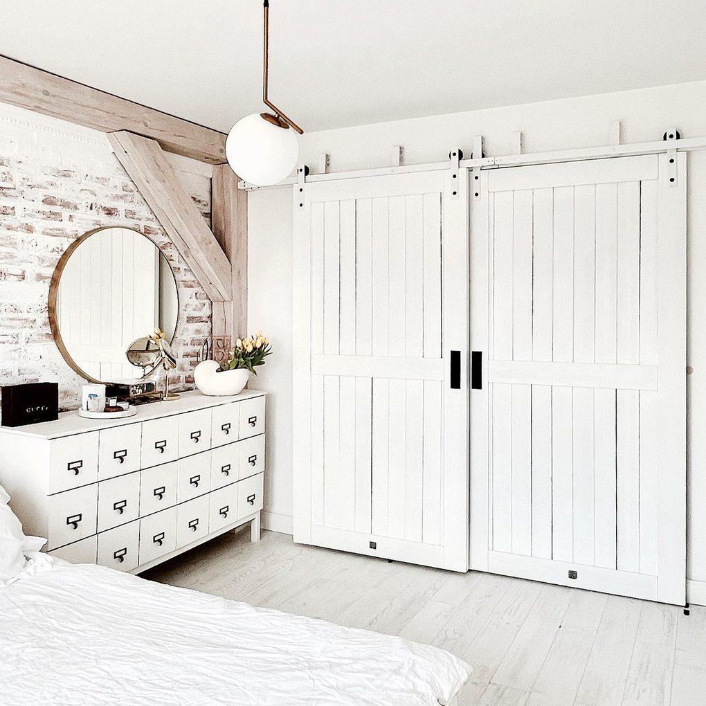 białe podwójne drzwi przesuwne w sypialni urządzonej w kolorach bieli