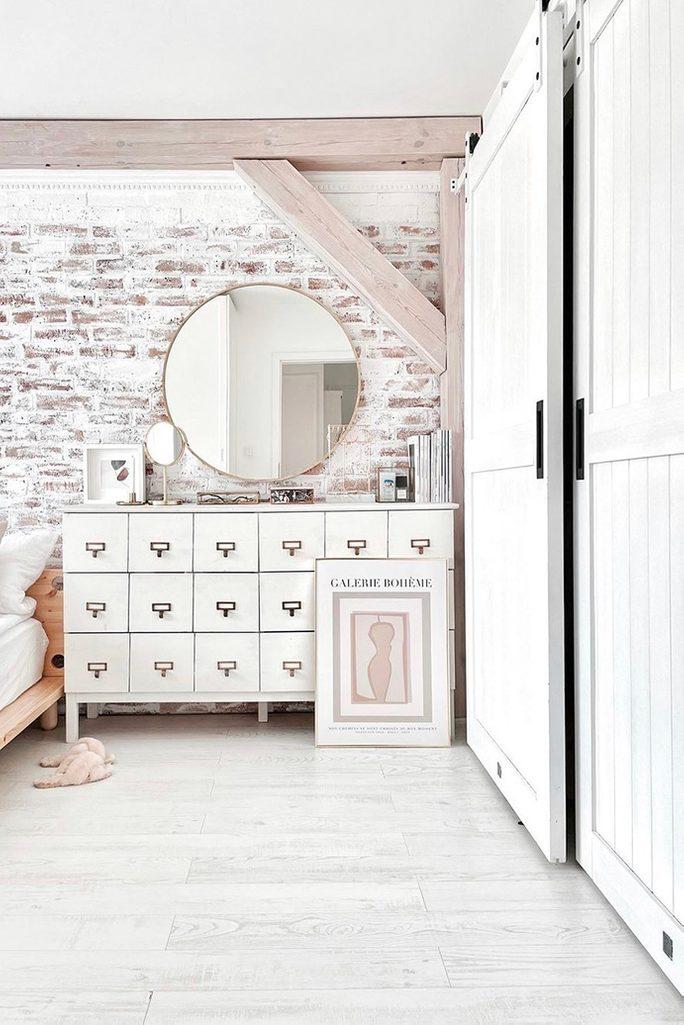 biała drewniana komoda na tle ceglanej ściany pomalowanej na biało
