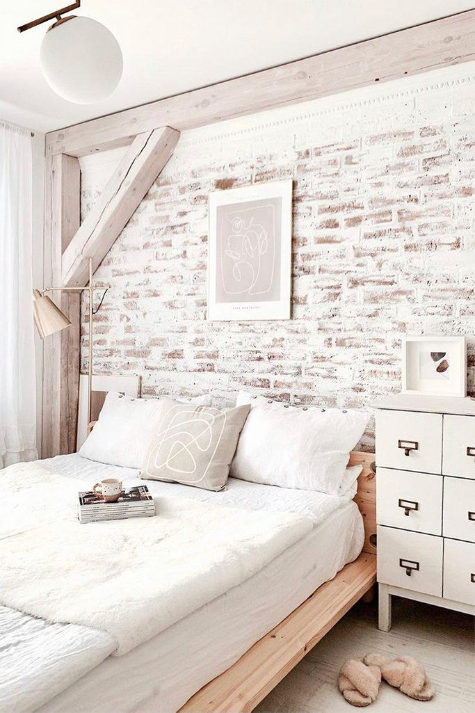 duże łóżko w sypialni z ceglaną ścianą pomalowaną na biało