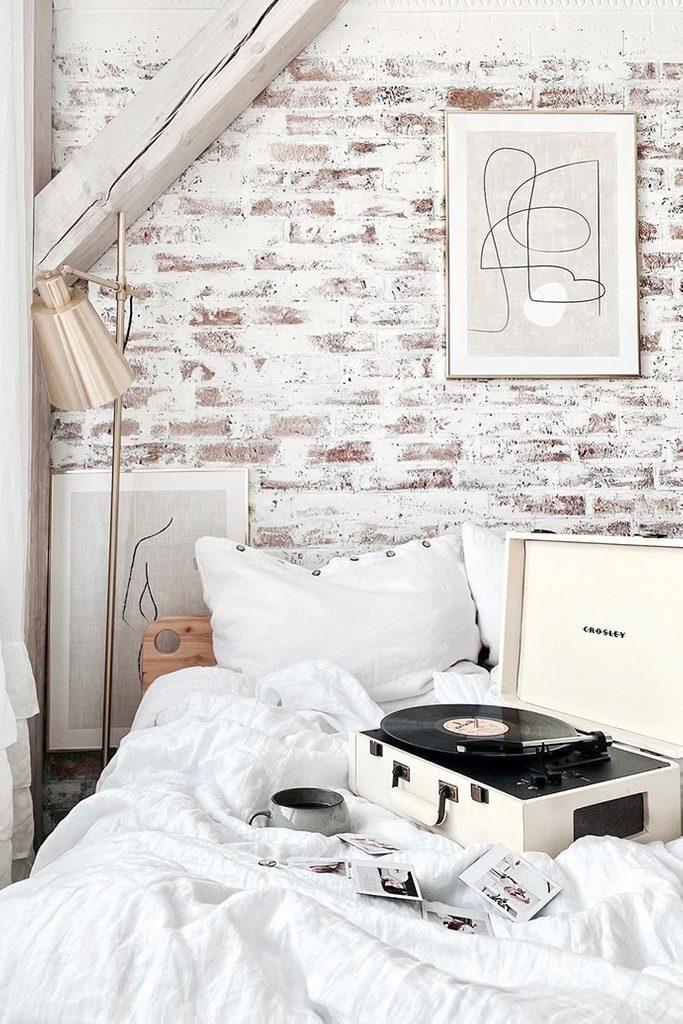 fragment sypialni w stylu modern rustic z ceglaną ścianą pomalowaną na biało