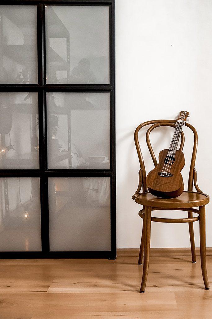 mała gitara na giętym krześle w stylu vintage obok drzwi ze szkłem