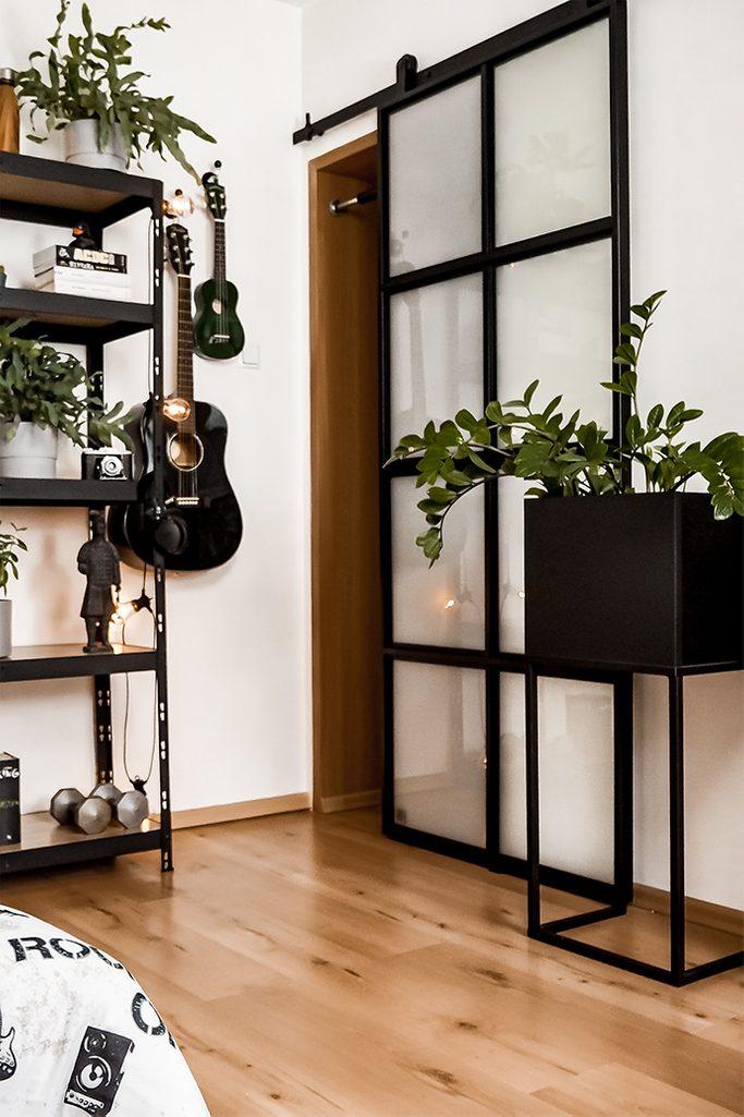 duży czarny metalowy stojak na kwiaty obok drzwi przesuwnych ze szkłem w metalowej ramie