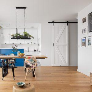 Jasny salon połączony z jadalnią i kuchnią, urządzony w bieli i drewnie w stylu california coastal