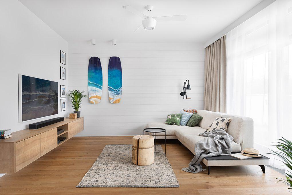 Przestronny, jasny salon z dużą jasną sofą urządzony w stylu california coastal z drewnem i bielą