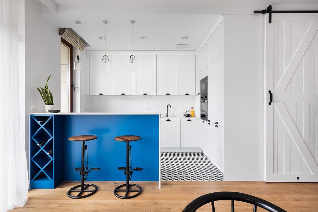 Otwarta kuchnia urządzona w bieli z czarnymi, metalowymi dodatkami oddzielona od salonu barkiem śniadaniowym wykończonym na niebiesko