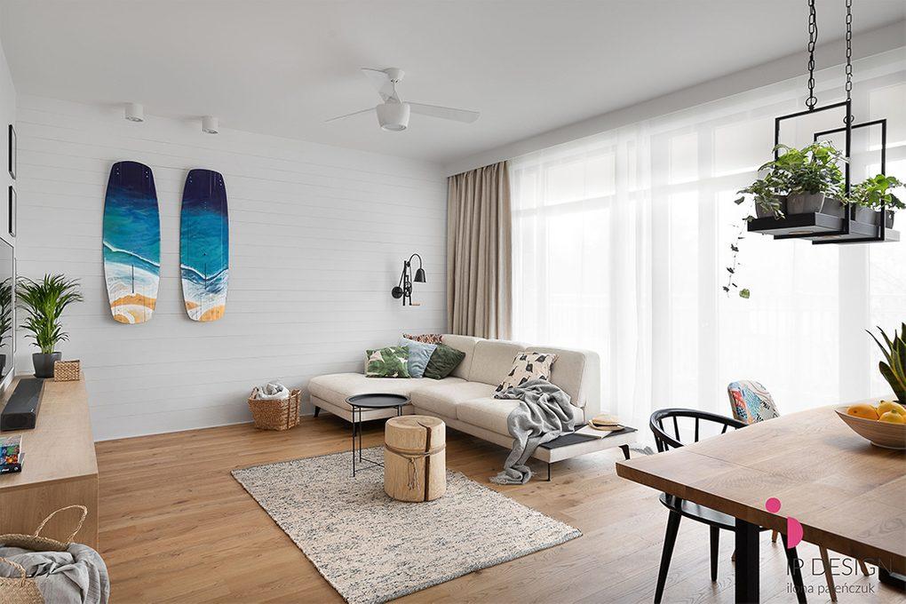 Jasny, przestronny salon z drewnianą podłogą, dużą jasną sofą i białymi ścianami