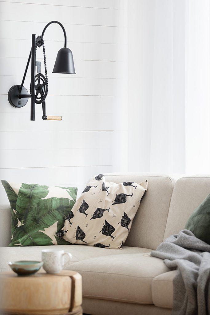 Czarna, loftowa lampa ścienna nad jasną sofą
