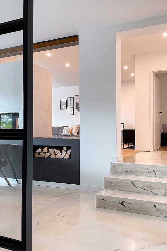 Nowoczesne wnętrze z białymi ścianami, jasną podłogą i czarnymi dodatkami
