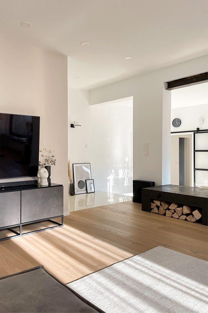 Salon z białymi ścianami, czarnymi metalowymi dodatkami utrzymany w stylu minimalistycznym