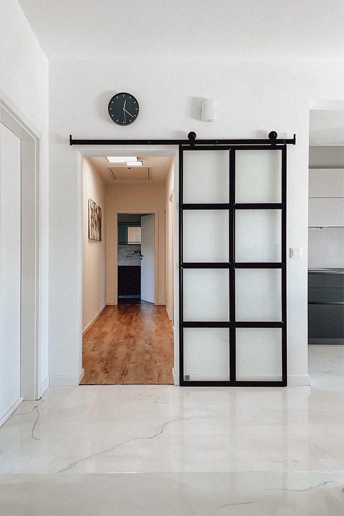 Szklane drzwi przesuwne w czarnej metalowej ramie zamykające korytarz