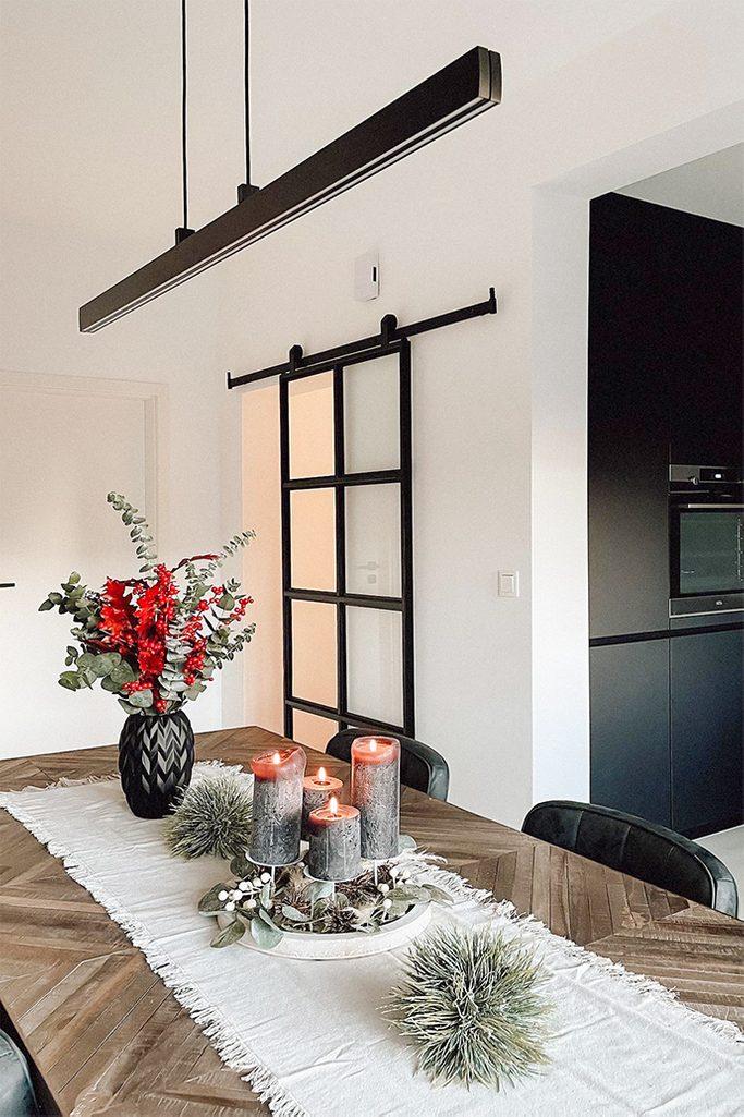 Dekoracyjne świece, wazon z suszonymi kwiatami na drewnianym stole jadalnianym oświetlonym długą, minimalistyczną lampą