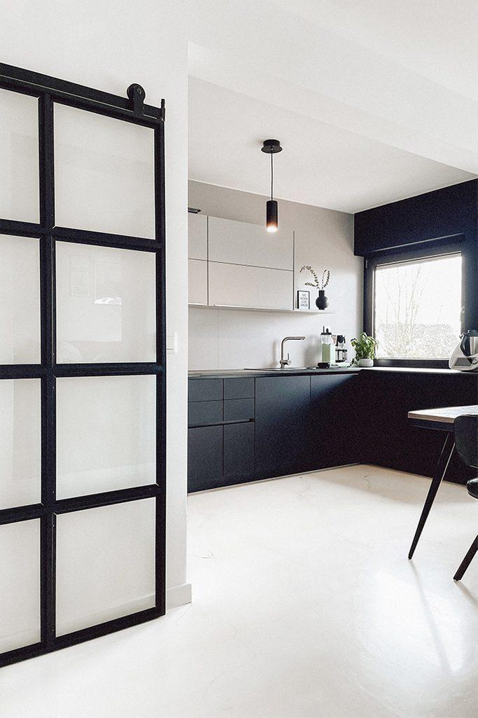 Czarno biała, otwarta kuchnia w minimalistycznym klimacie z jasną podłogą