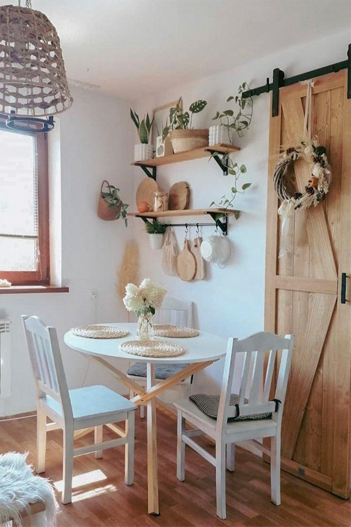 biały okrągły stół z białymi krzesłami stojący przy ścianie, na której wiszą półki z roślinami