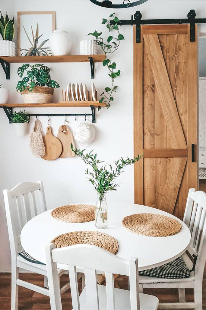 biały okrągły stół z białymi krzesłami stojący przy ścianie udekorowanej drewnianymi półkami i drewnianymi drzwiami przesuwnymi