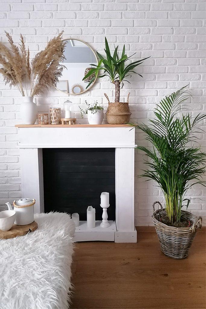 kominek przy ścianie z białej cegły ozdobiony roślinami i dekoracjami w stylu boho
