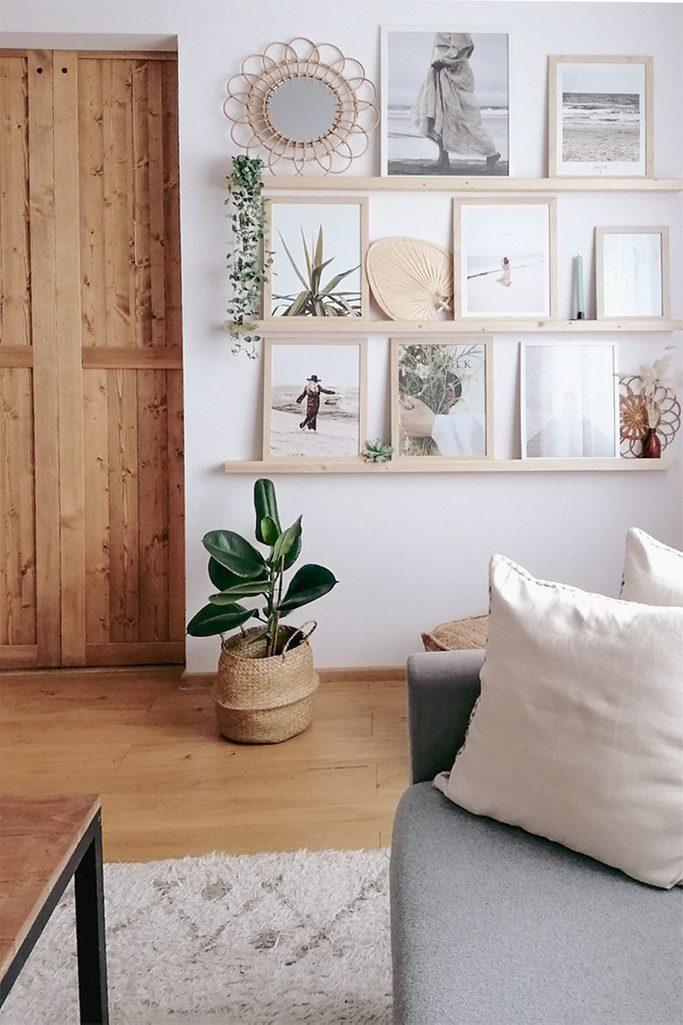 galeria obrazów w drewnianych ramkach na białej ścianie w salonie