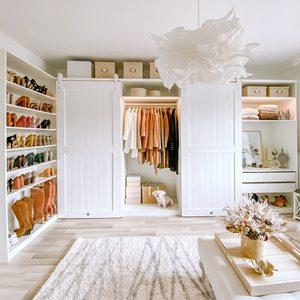 Białe drewniane drzwi przesuwne do szafy w aranżacji dużej garderoby w sylu klasycznym