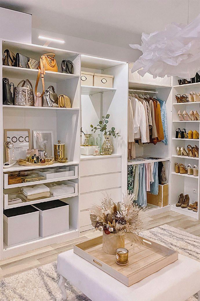 Buty, ubrania i torebki ułożone na białych półkach i regałach w aranżacji garderoby