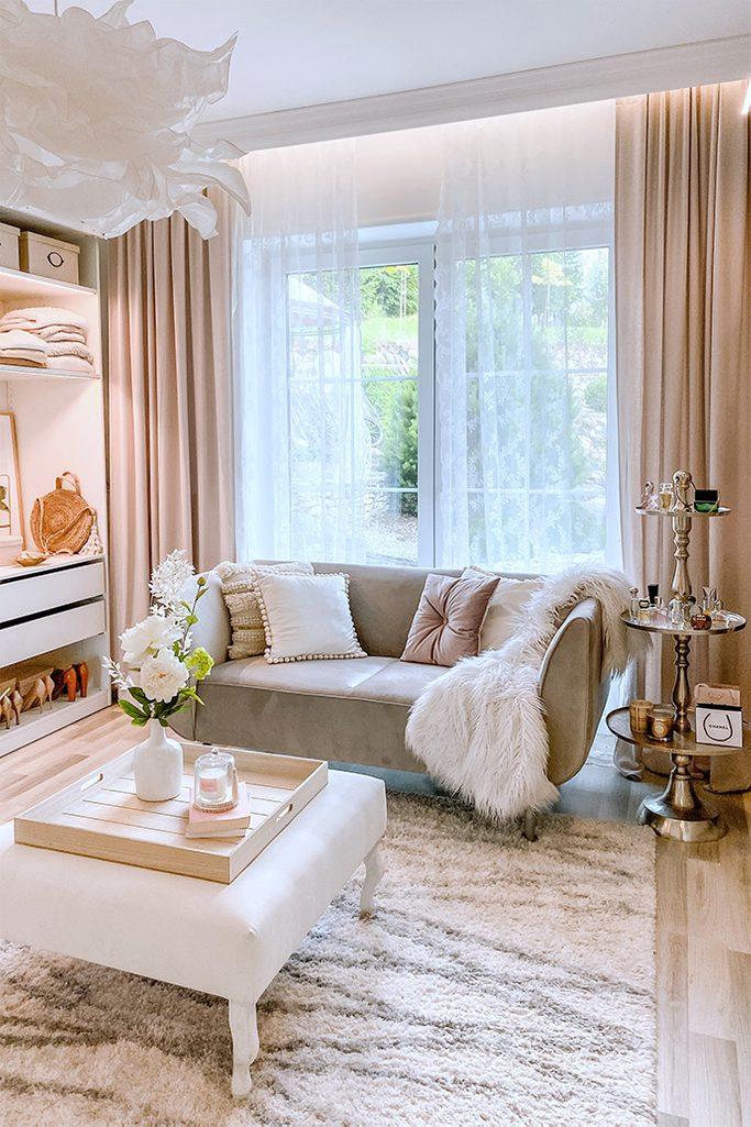 Białe siedzisko i szara sofa w jasnej aranżacji garderoby
