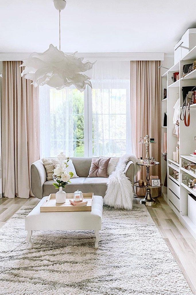 Białe siedzisko i szara sofa w jasnej aranżacji dużej garderoby