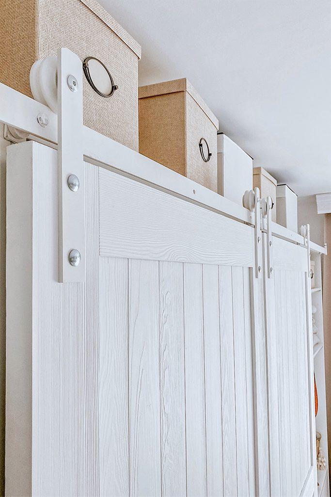 Białe drewniane drzwi na białym systemie przesuwnym