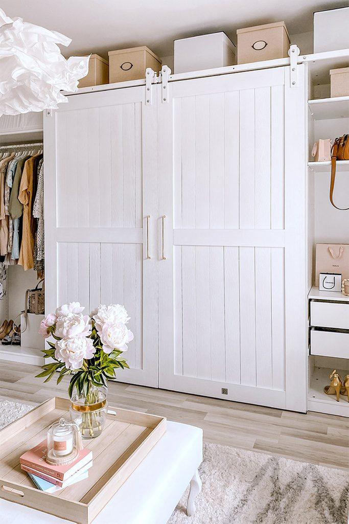 Duże białe drzwi dwuskrzydłowe na białym systemie przesuwnym w aranżacji garderoby