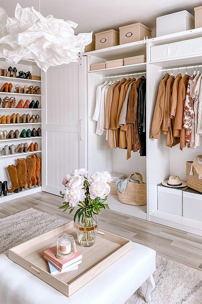 Duży pokój z otwartymi szafami ukazującymi ubrania oraz półkami wypełnionymi damskimi butami