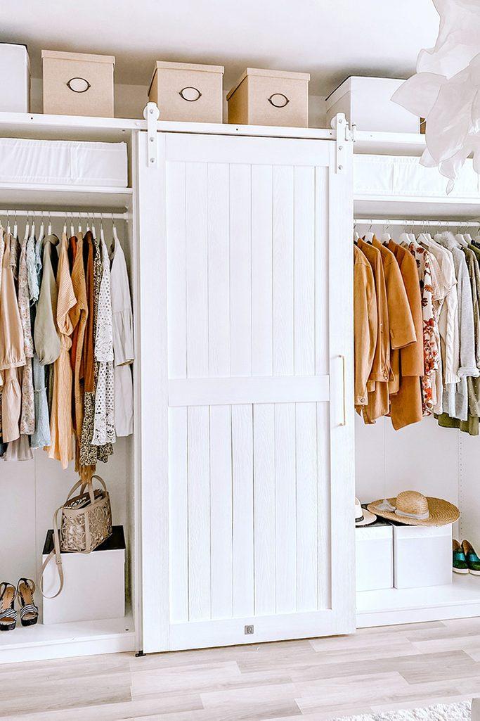 Białe, drewniane drzwi na systemie przesuwnych zamykające szafy z ubraniami