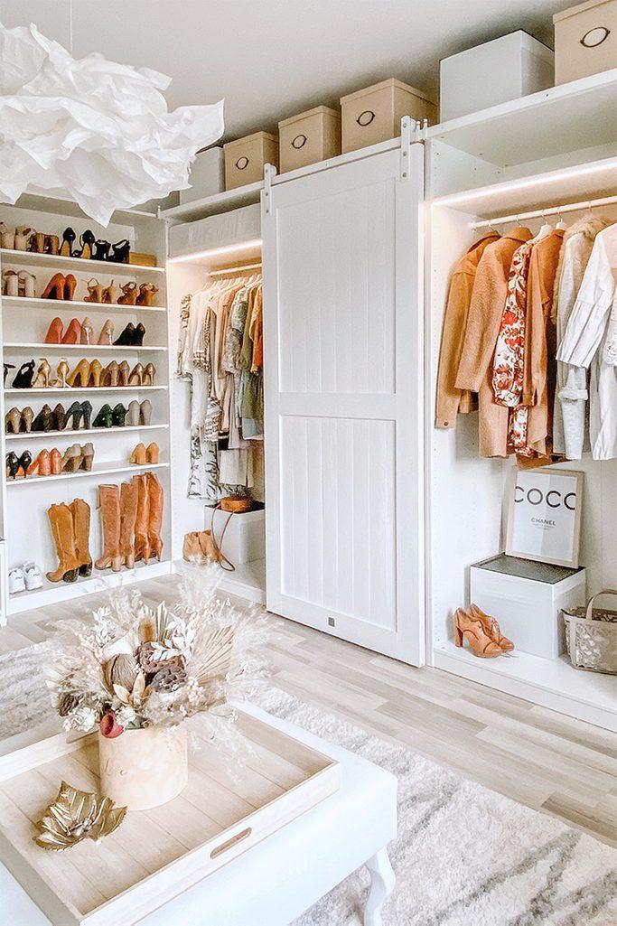 Białe szafy z ubraniami i białe półki z damskim obuwiem w dużej garderobie